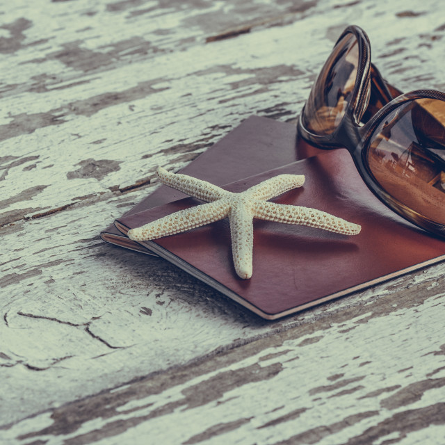"""""""Travel, holiday and vacation in the summer tranquility and relaxation concept with passports starfish and sunglasses on a grunge wooden table. Selective focus macro close up."""" stock image"""