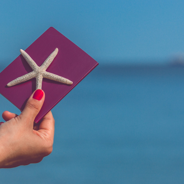 """""""Hand holding passport and starfish with blue sea ocean and sky in the background. Concept for travel, holiday, vacation, getaway tranquility and relax."""" stock image"""