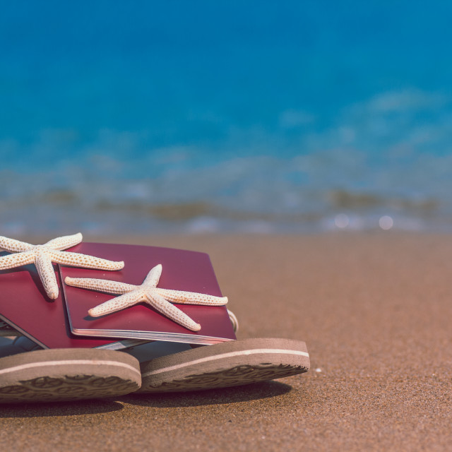"""""""Flip flops with passport and starfish on the sand beach with blue ocean sea waves in the background. Concept for travel, holiday, vacation, getaway tranquility and relax."""" stock image"""