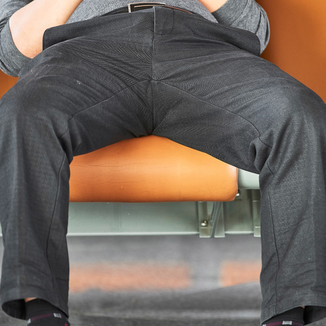 """""""Man sitting with legs spread wide open"""" stock image"""
