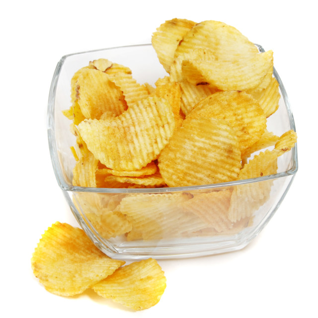 """""""Heap of fried potato chips in glass bowl on white background."""" stock image"""