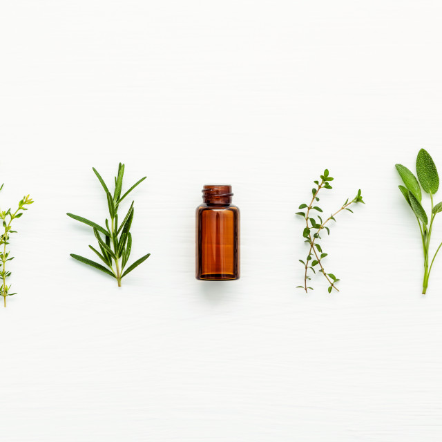 """Bottle of essential oil with fresh herbal sage, rosemary, lemon thyme and..."" stock image"