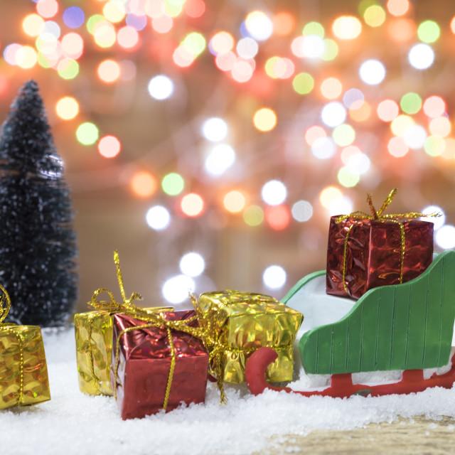 """Sleigh and gift boxes on bokeh christmas light background."" stock image"