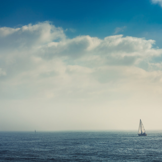 """Sail boat in the foggy sea in a calm early morning"" stock image"