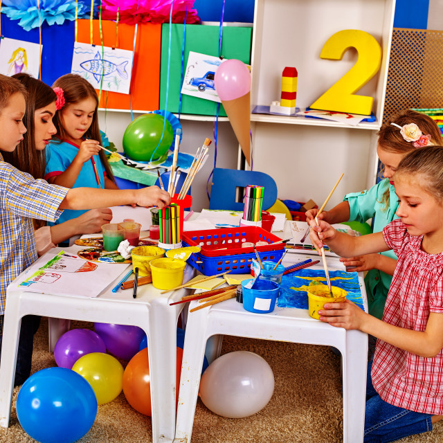 """Woman teaches children to handicrafts made of paper in kindergarten ."" stock image"