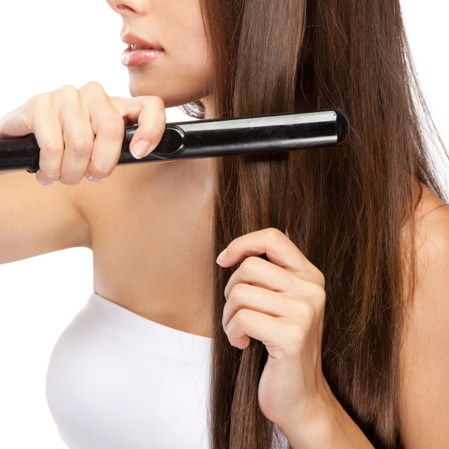 """Young woman iwth a hair straightener"" stock image"