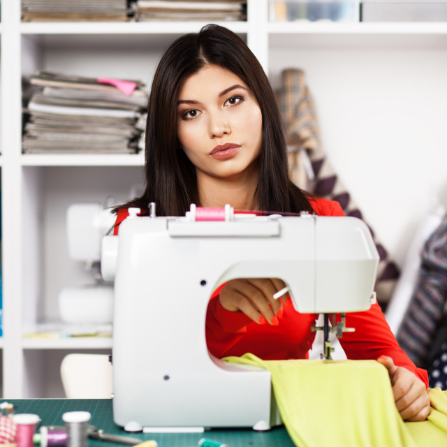 """Young woman at a sewing machine"" stock image"