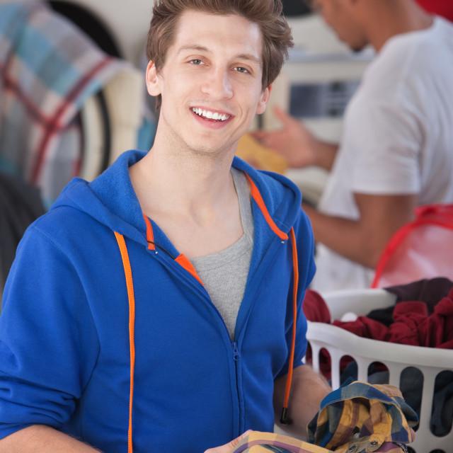 """Smiling Man In Laundromat"" stock image"