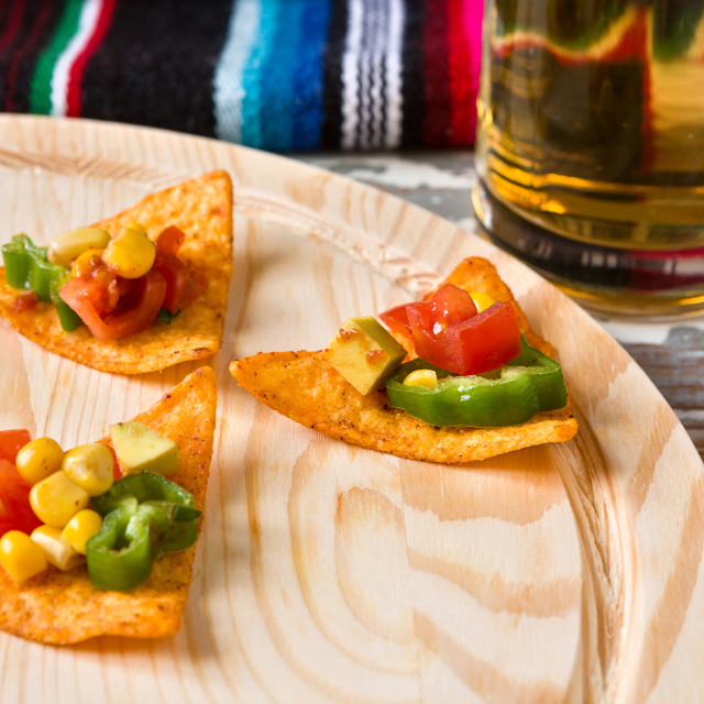 """Close up of nachos chips with vegetables and beer"" stock image"