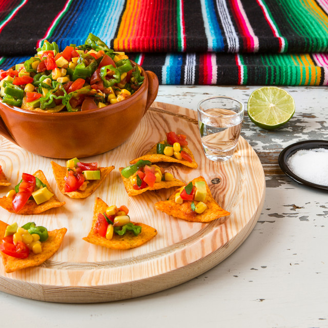 """Nachos chips and vegetables in an earthenware bowl and tequila with a poncho on background"" stock image"