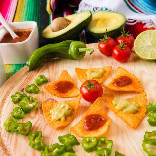 """Nachos chips and vegetables on a chopping board"" stock image"