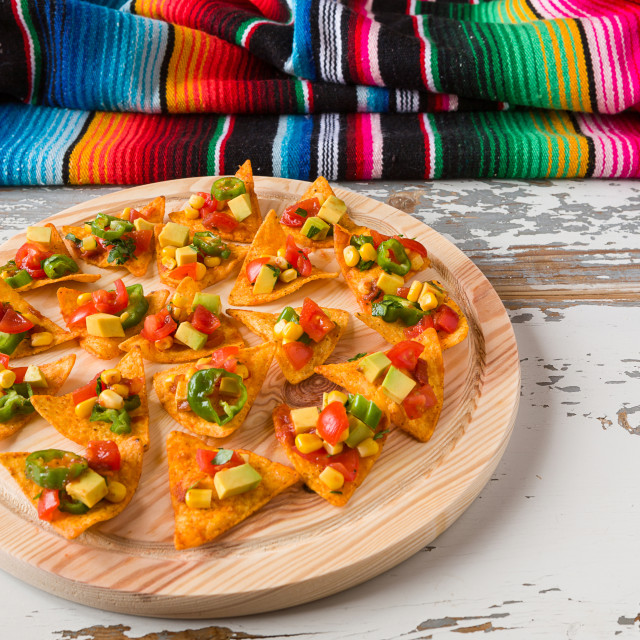 """Nachos chips with vegetables on a chopping board and a poncho"" stock image"