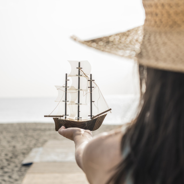 """Woman hold boat model on the beach"" stock image"