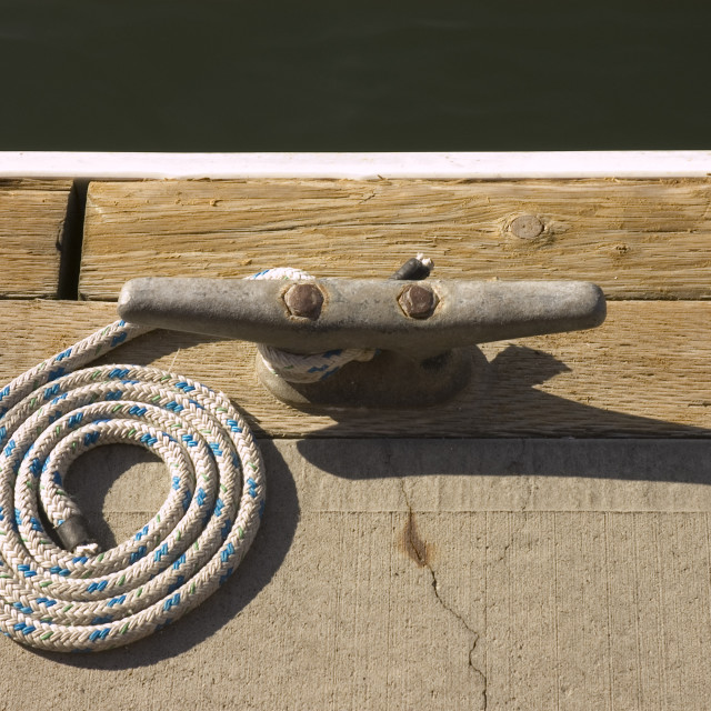 """""""Rope coiled up attached to cleat awaiting boat to dock"""" stock image"""