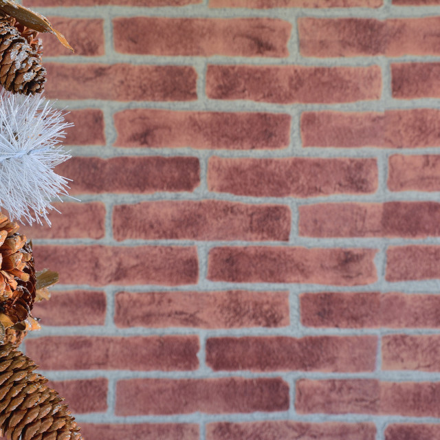 """""""Close up of decorative Christmas cones at left side against of brick wall"""" stock image"""