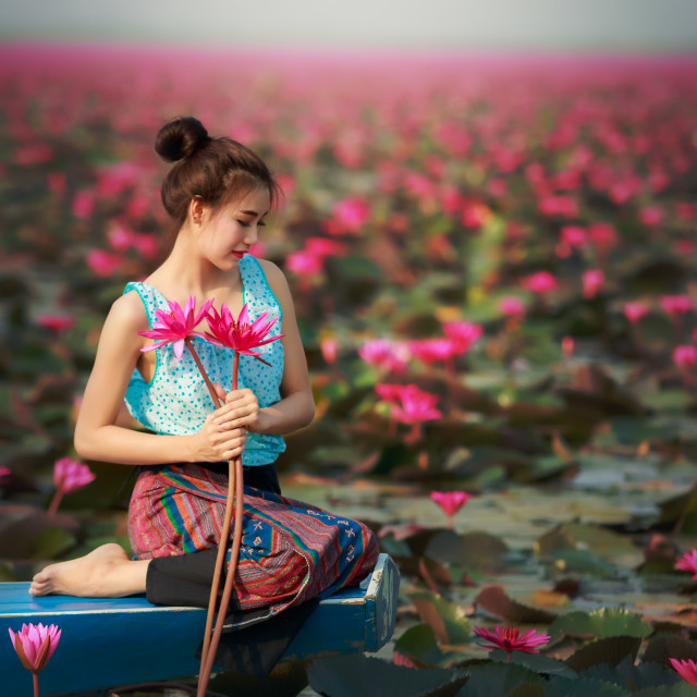 """Rural girl sitting in boat in the lotus field."" stock image"