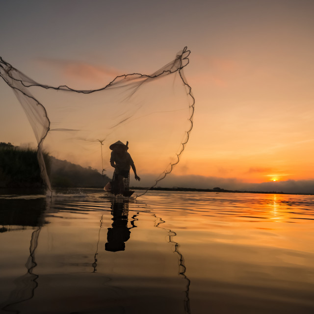 """Fisherman throwing net at the river."" stock image"