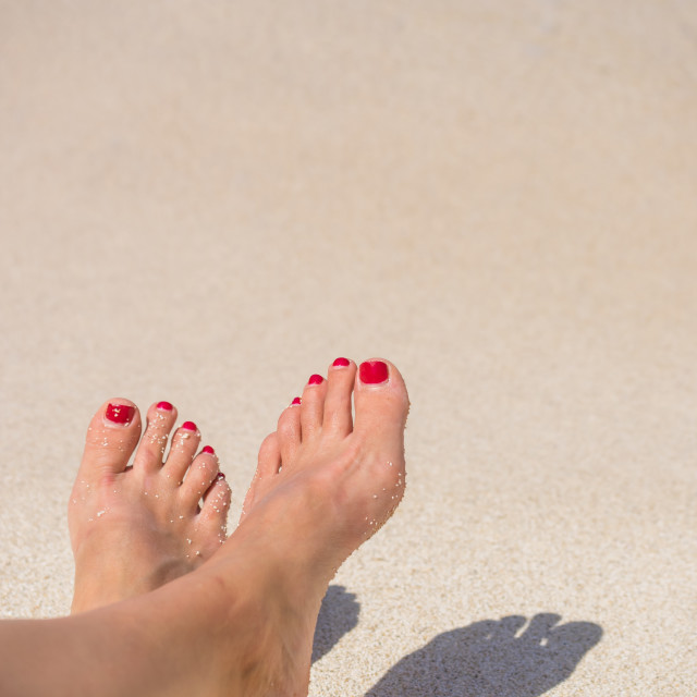 """Woman feet closeup of girl relaxing on beach"" stock image"
