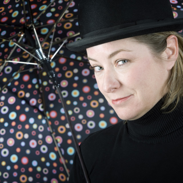 """Woman in a bowler hat with umbrella"" stock image"