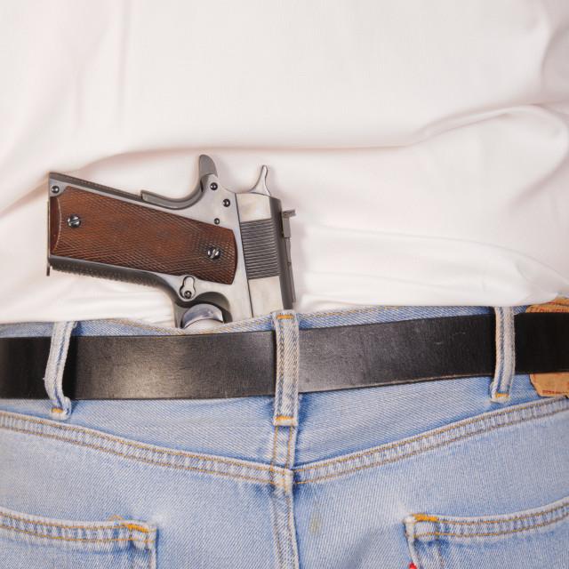 """semi-automatic pistol stuck in waistband"" stock image"