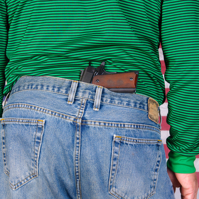 """""""Man with a semi-automatic pistol stuck in his waistband in front of an American flag"""" stock image"""