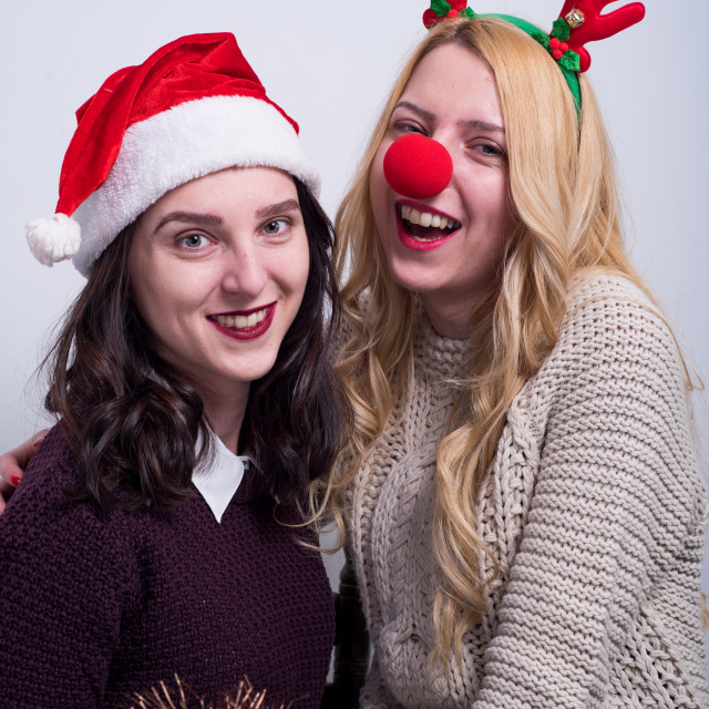 """happy sisters with Santa hat and deer horns"" stock image"