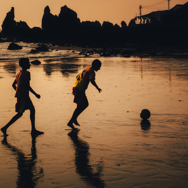 """Two boys play soccer on beach in dusk, Goa, India"" stock image"