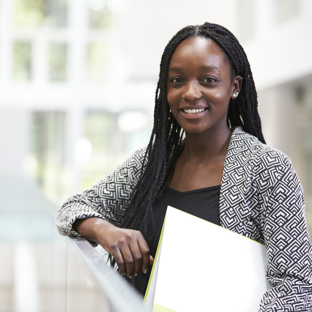"""Smiling young black female student in university foyer"" stock image"