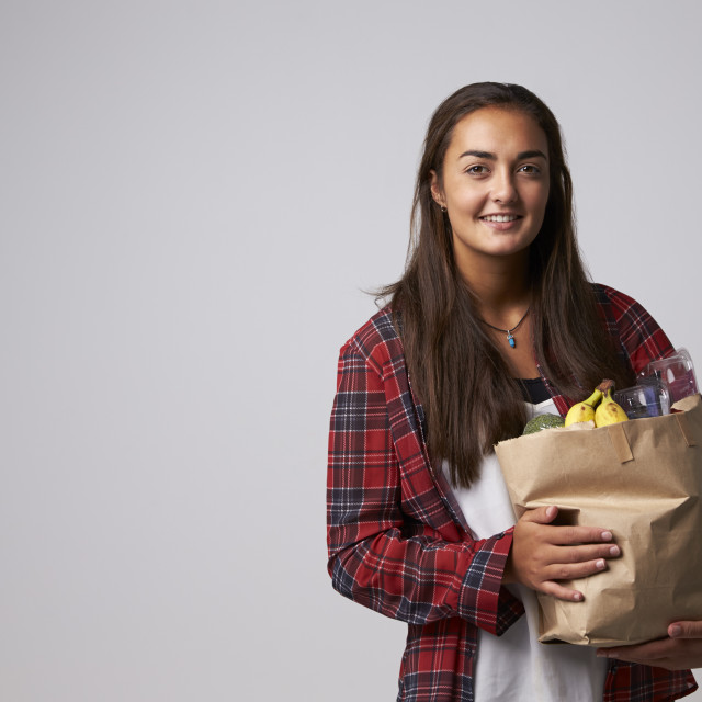 """Studio Portrait Of Female Nutritionist With Bag Of Food"" stock image"