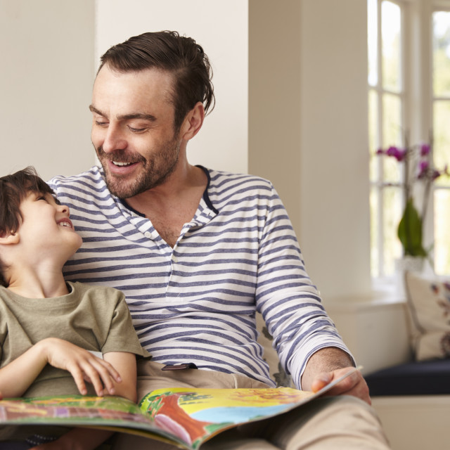 """Father And Son Reading Story At Home Together"" stock image"