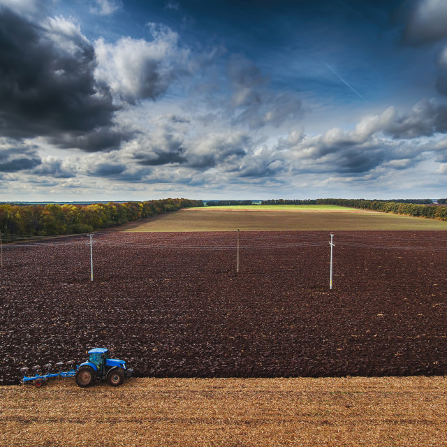 """Tractor cultivating field at autumn"" stock image"