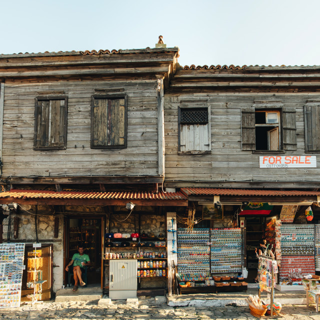 """Souvenirs seller sits in his shop in the old part of Nessebar. The ramshackle building for sale in Old Town."" stock image"