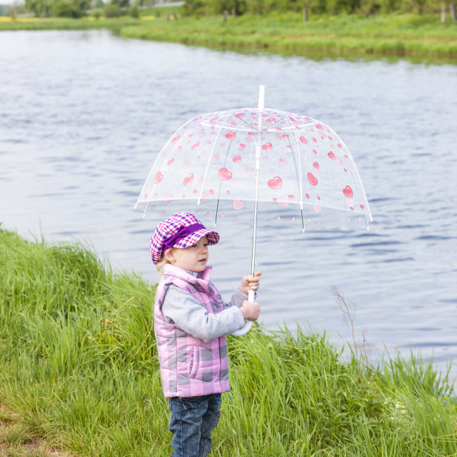 """little girl with umbrella in spring nature"" stock image"
