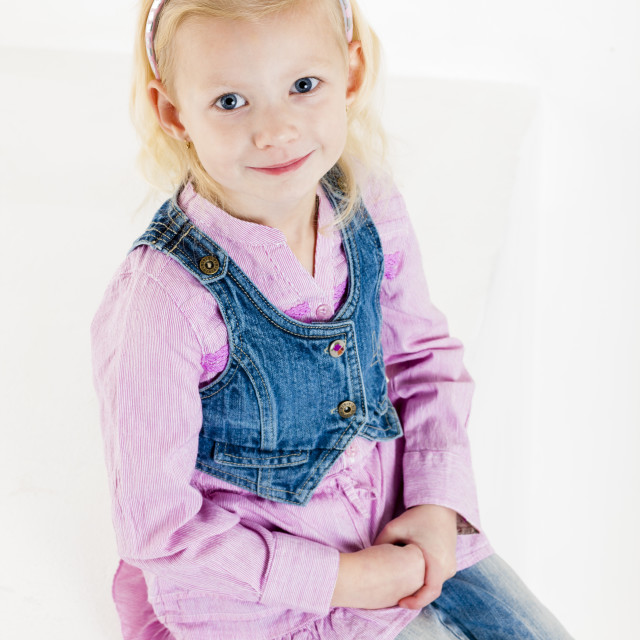 """portrait of sitting little girl wearing jeans"" stock image"