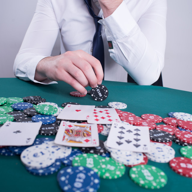 """""""poker player holding chip in hand"""" stock image"""