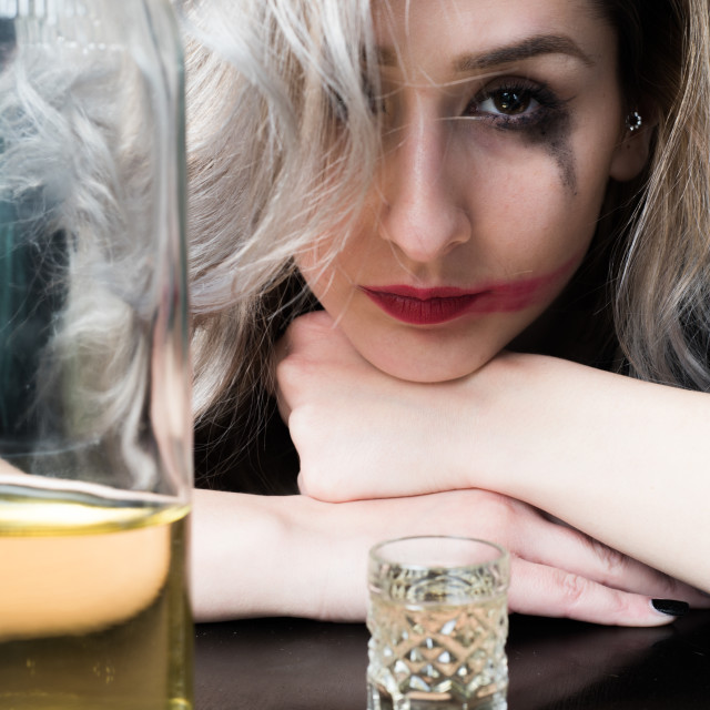 """depressed woman with bottle of alcohol near her"" stock image"