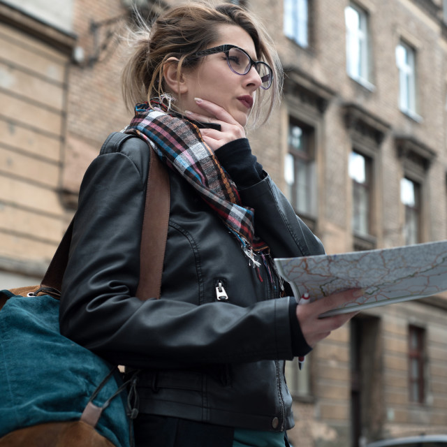 """woman holding map and looking in distance"" stock image"