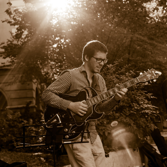 """""""Young man playing passionately solo on a black jazzy guitar"""" stock image"""