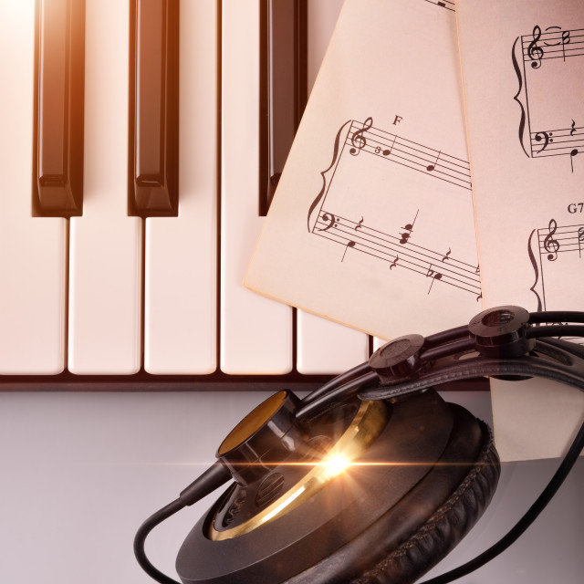 """Electronic piano keyboard with headphones and sheet music top"" stock image"