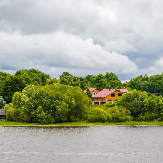 """Small houses on the opposite side of the river"" stock image"