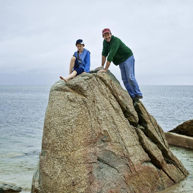 """Dad and daughter climb beach boulder"" stock image"