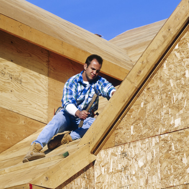 """""""HOUSE UNDER CONSTRUCTION WITH WORKER ON ROOF."""" stock image"""