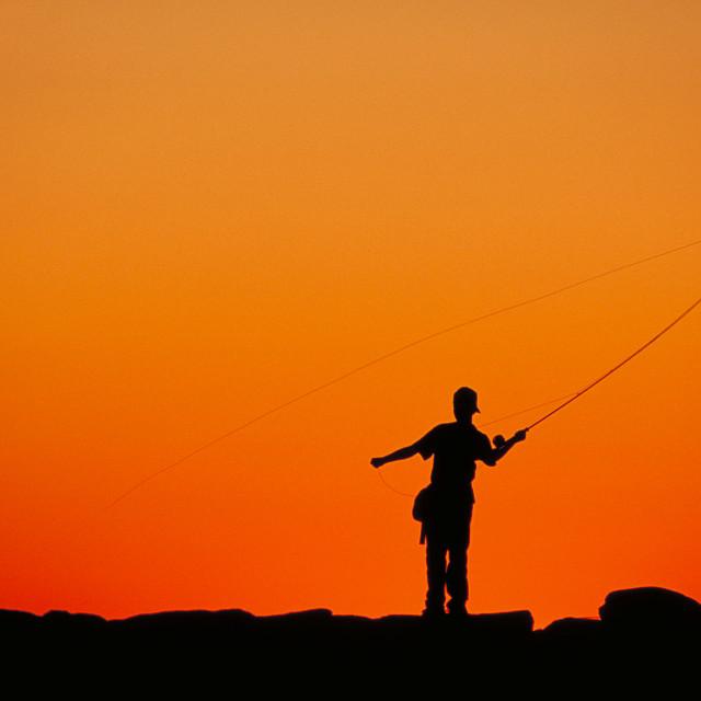 """Boy fishing from a jetty at sunset, Menemsha, Martha's Vineyard"" stock image"