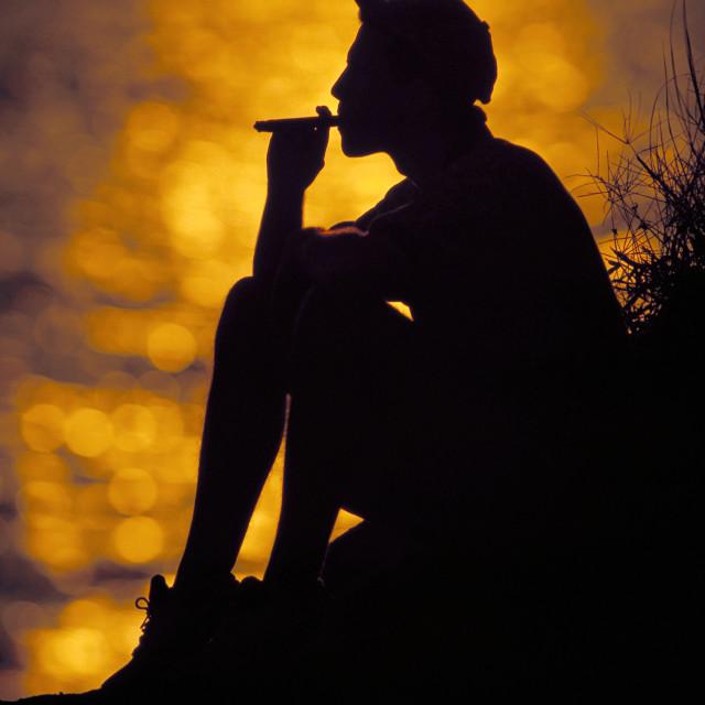 """Man in silhouette smoking a cigar."" stock image"