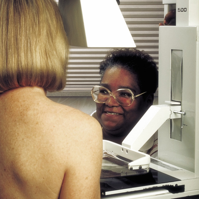 """""""Radiology technician performs mammography test on female patient."""" stock image"""