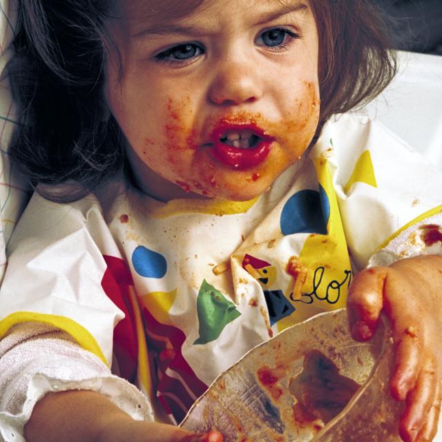 """Toddler making a mess while eating pasta."" stock image"