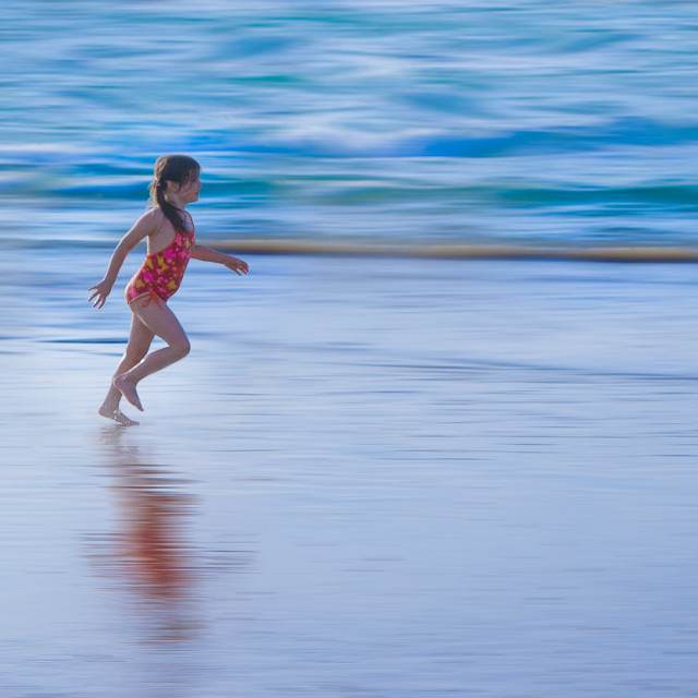 """Girl running on the beach at water line"" stock image"
