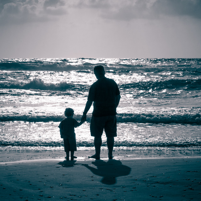 """Hand in hand on the beach at water front"" stock image"