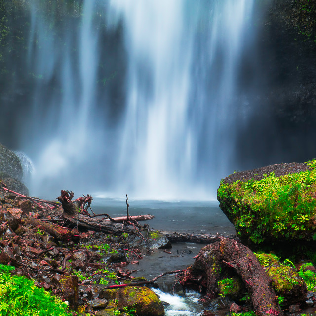 """Green rock in front of a wide waterfall"" stock image"