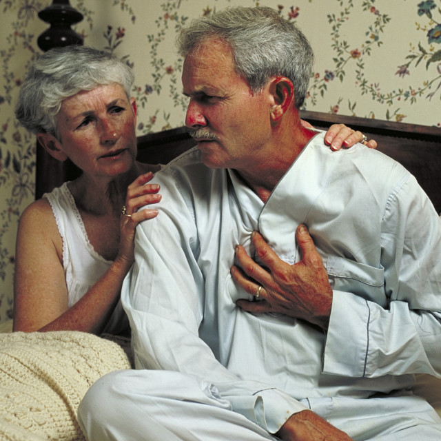 """""""Senior man holds his chest in pain as his concerned wife looks on."""" stock image"""